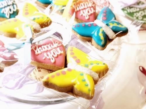 """タイニーケークの""""Thank you""""と描かれたハート形と蝶のカラフルアイシングクッキー"""