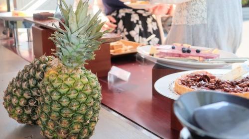 パイナップルとその向こうに見えるタルトやムースなど数種類のカウンター