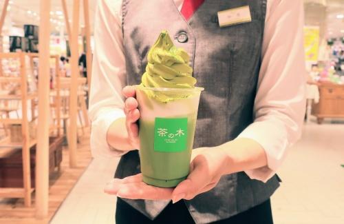 抹茶ラテにソフトクリームが乗ったドリンクを店員さんが持つ様子