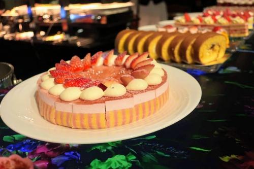 いちごが飾られたムース状のホールケーキとロールケーキ