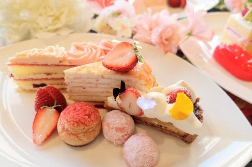 お花飾りに囲まれたお皿に盛られている苺ケーキ3種類