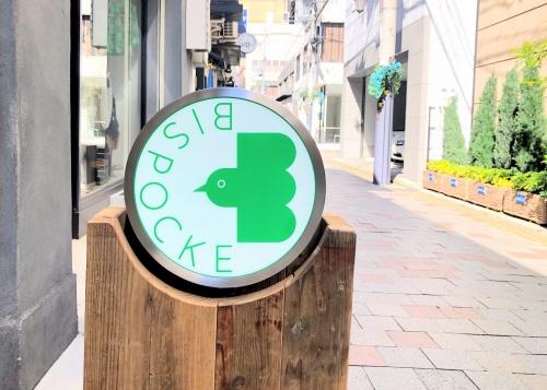 緑の鳥をロゴにしたビスポッケ神戸の看板
