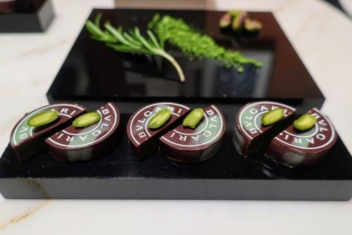 ローズマリー、抹茶、ピスタチオが添えられた円型チョコレート